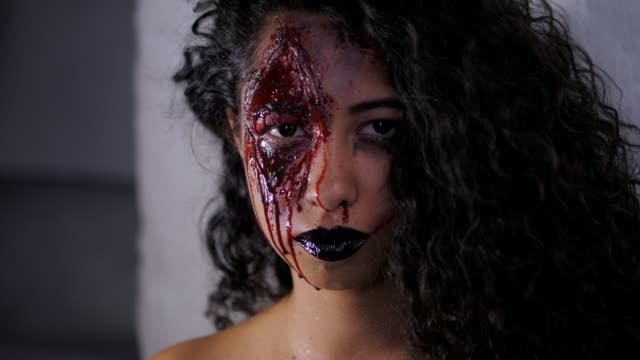 Aterrador-retrato-de-muchacha-joven-zombie-con-maquillaje-de-Halloween-sangre-Hermosa-mujer-latina-con-cabello-rizado-en-cámara-en-estudio-Cámara-lenta