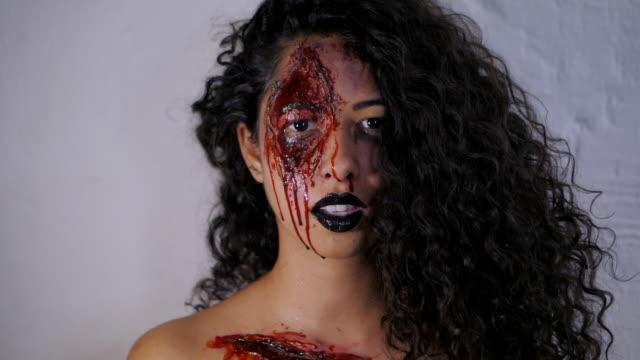 Beängstigend-Porträt-des-jungen-killer-Mädchen-mit-Halloween-Blut-Make-up-Schöne-Latin-Frau-mit-lockigem-Haar-in-Kamera-im-Studio-Slow-motion