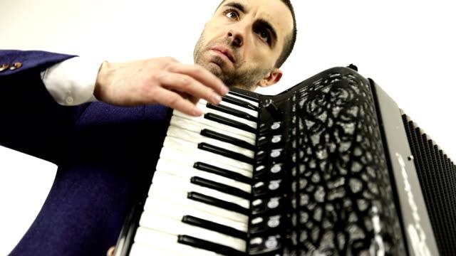 Un-músico-serio-centrado-en-un-traje-de-moda-disfruta-de-tocar-el-acordeón-