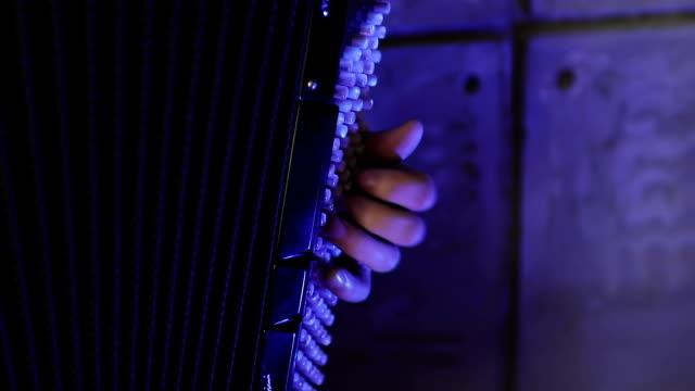 Primer-plano-de-un-hombre-de-izquierda-de-mano-tocando-un-acordeón-negro-