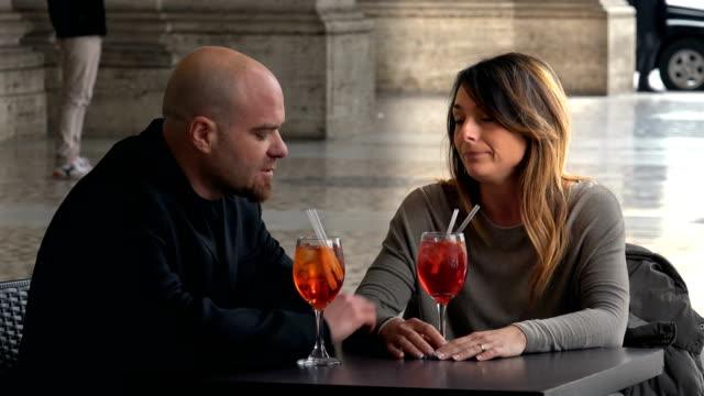 traurig-paar-sprechen-und-trinken-einen-Cocktail-sprechen-über-ihre-Beziehung