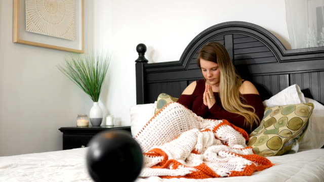 Woman-praying-in-her-bedroom-before-going-to-sleep