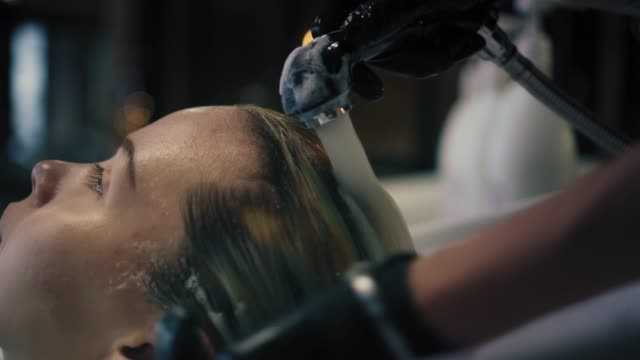 Hairdresser-in-black-gloves-carefully-washes-female-s-hair-with-conditioner-in-sink-in-hair-salon-and-then-turns-off-the-water-Closeup