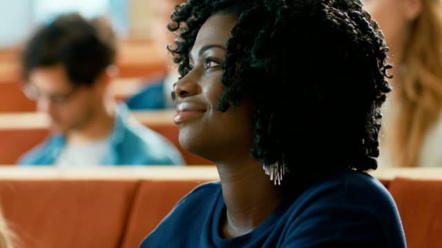 Retrato-de-una-muchacha-negra-joven-inteligente-y-hermosa-escuchar-una-conferencia-en-un-aula-llena-de-estudiantes-Multi-étnica-Estudio-en-la-Universidad-de-los-jóvenes-