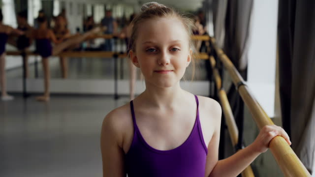 Portrait-of-beautiful-little-girl-starting-ballet-dancer-looking-at-camera-and-smiling-standing-in-ballet-class-in-spacious-light-dancehall-Art-and-childhood-concept-