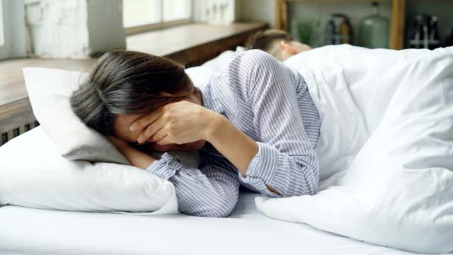Traurige-Frau-ist-Pyjamas-im-Bett-liegend-und-weinend-nach-Kampf-mit-ihrem-Mann-der-neben-ihr-mit-dem-Rücken-zu-ihr-liegt-Schwierigkeiten-im-Eheleben-Konzept-