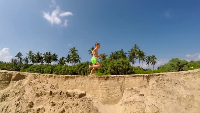 Running-little-boy-by-the-sandy-sea-beach-with-a-green-palm-trees-and-blue-sky-background-slow-motion-footage