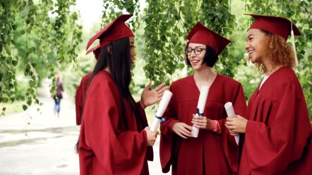 Fellow-students-are-talking-and-laughing-after-graduation-ceremony-holding-diplomae-and-wearing-gowns-and-mortarboards-girls-are-sharing-memories-and-expressing-hopes-