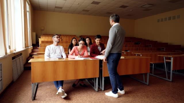 Profesor-llega-al-aula-y-empieza-a-hablar-a-los-estudiantes-comienza-la-Conferencia-los-estudiantes-tomando-taxtbooks-y-escuchar-al-educador-Aprendizaje-y-la-enseñanza-el-concepto-