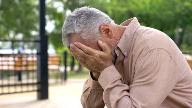 Triste-anciano-sentado-en-el-Banco-del-hospital-jardín-pensionista-llorando-de-tristeza