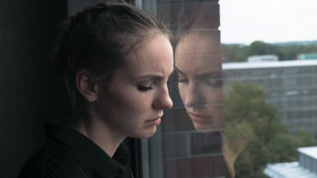 Traurige-junge-Frau-schiefen-Kopf-gegen-Glasfenster