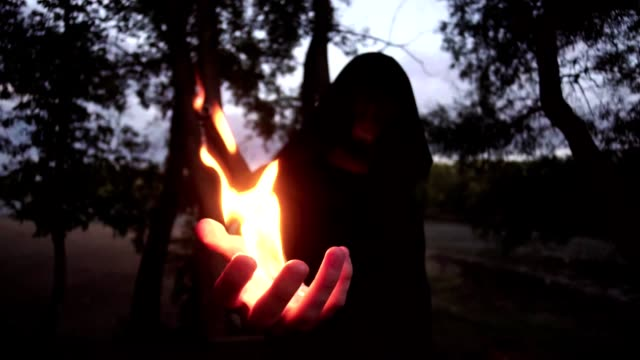 a-fire-mage-in-a-black-raincoat-outdoors-with-a-sword-behind-his-back-taming-the-fire-with-your-hand