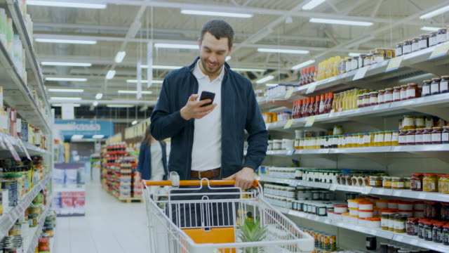 At-the-Supermarket:-Handsome-Man-Uses-Smartphone-Smiles-while-Standing-at-the-Canned-Goods-Section-Has-Shopping-Cart-with-Healthy-Food-Items-Inside-Other-Customers-Walking-in-Background-