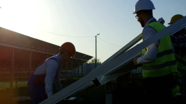 Three-workers-install-a-solar-panel