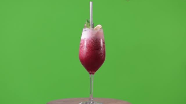 Rot-auf-grünem-Hintergrund-cocktail-cocktail-dreht-auf-Hromokoy-Hintergrund-alkoholischen-Cocktail-auf-grünem-Hintergrund