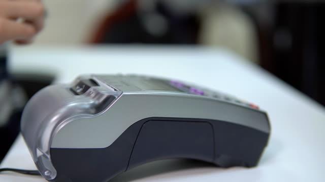 Momento-de-pago-con-tarjeta-de-crédito-a-través-de-terminal-en-la-tienda-de-ropa-