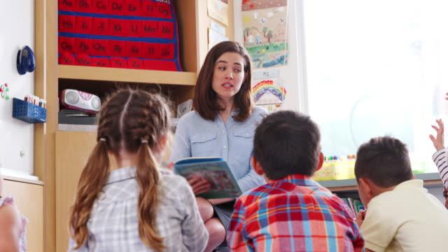 Grundschule-Kinder-Anhebung-Hände-Lehrer