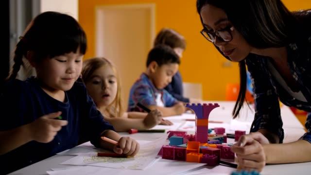 Maestro-de-jardín-de-niños-ayudando-a-niños-en-clase-de-arte