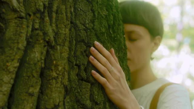 Niña-abraza-a-un-árbol-grande-en-el-bosque-