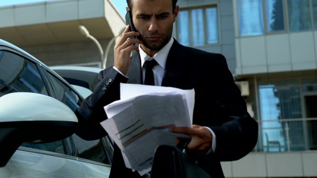 Business-person-talking-on-phone-near-car-solving-financial-issues-of-company
