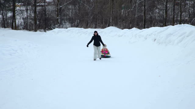 Woman-Pulling-a-Snow-Tube-with-Little-Girl