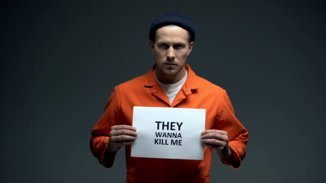 Caucasian-male-prisoner-holding-They-wanna-kill-me-sign-calling-for-help