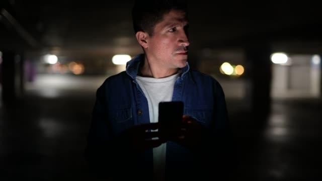 Sospechoso-mirar-hombre-hispano-pensando-mientras-se-usa-el-teléfono-en-el-estacionamiento-oscuro