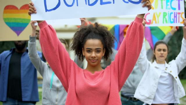 Frau-hält-Liebe-ohne-Grenzen-Plakat-zusammen-mit-LGBT-Aktivisten-Stolz