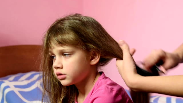 Mother-combing-her-long-hair-girls-and-braid-them-into-a-pigtail