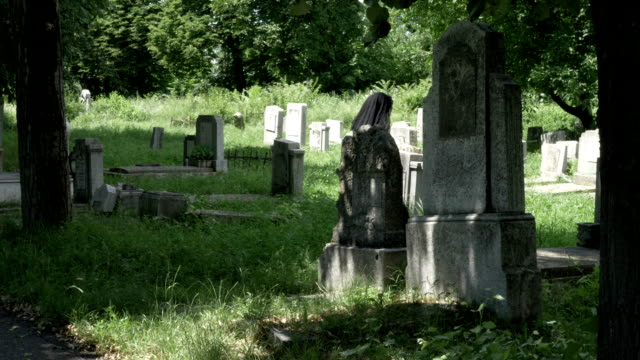 Woman-filled-with-sadness-looking-from-lost-beloved-grave-walking-in-graveyard