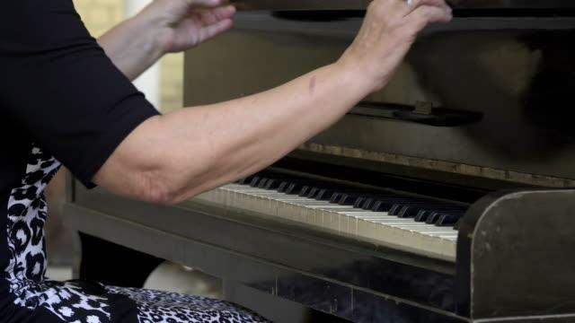 Mujer-Abra-la-tapa-y-comience-a-jugar-el-piano