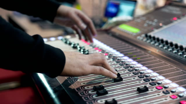 Audio-engineer-working-on-a-professional-console-moving-faders-mixing-music