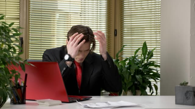 Young-guy-in-a-suit-is-sitting-at-the-office-working-on-a-laptop-tired-falling-asleep-bored-60-fps