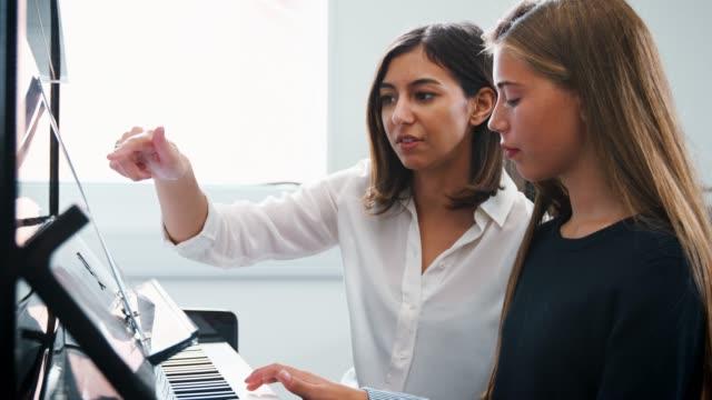 Weibliche-Schüler-mit-Lehrer-im-Musikunterricht-Klavier-zu-spielen
