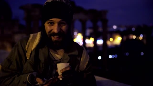 smiling-an-happy-homeless-in-the-night-showing-his-alms