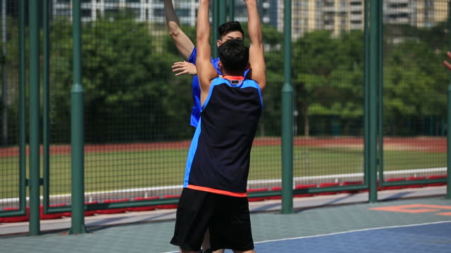 young-asian-adults-playing-basketball-outdoors