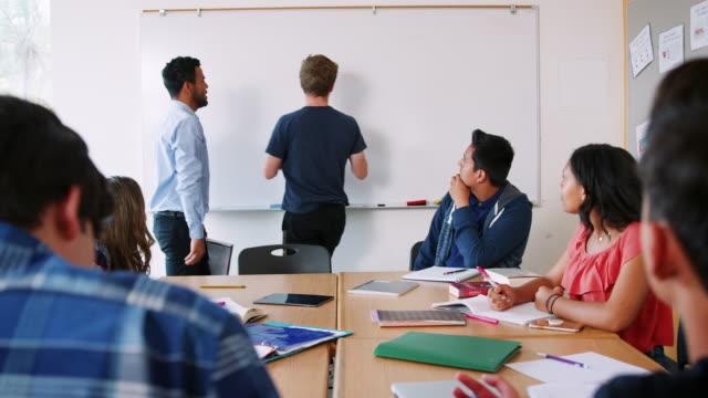 Männlich-Gymnasium-Schüler-schreiben-auf-Whiteboards-In-Mathematik-Klasse