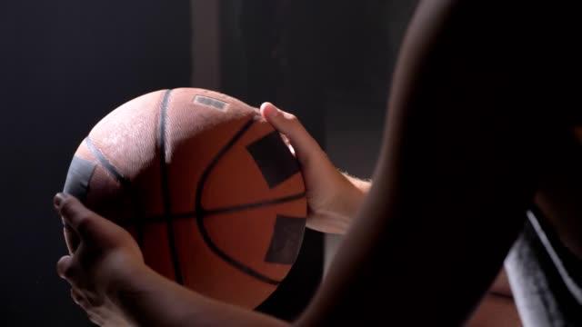 Jugador-de-baloncesto-sentado-y-jugando-con-la-pelota-esperando-para-ir-al-patio-en-cuarto-oscuro-brumoso