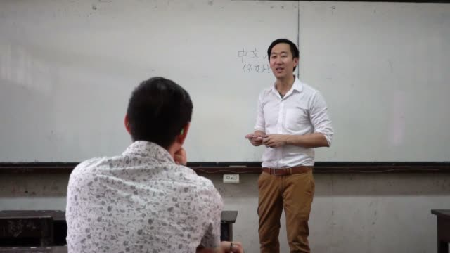 Instructor-de-idiomas-orientales-extranjeros-asiáticos-jóvenes-dando-una-lección-de-lengua-en-el-aula
