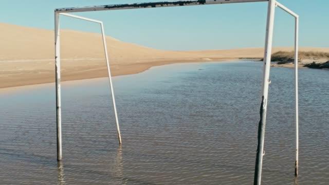 imágenes-aéreas-de-una-hermosa-laguna-azul-junto-a-las-dunas-de-desierto-con-una-puerta-de-fútbol-en-el-agua