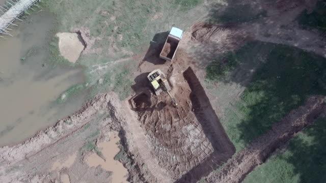Antena:-visión-estática-de-una-excavadora-cargando-tierra-en-un-pequeño-camión