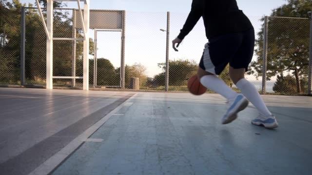 Niedrigen-Winkel-Aufnahmen-von-einer-professionellen-weiblichen-Basketballspieler-in-Aktion-Mädchen-üben-im-Freien-auf-dem-Platz-einen-Ball-ins-Netz-zu-werfen-Ansicht-der-Rückseite
