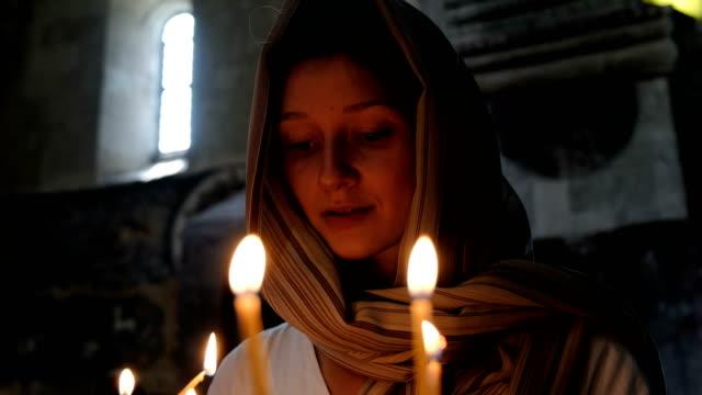 Mujer-en-velo-pone-una-vela-y-reza-ante-el-icono-en-la-iglesia-católica-ortodoxa