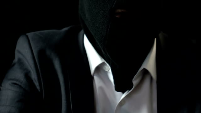 Mafiosi-in-face-mask-aiming-pistol-at-camera-contract-killing-blackmail-crime