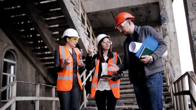 El-capataz-y-los-inspectores-de-dos-mujeres-para-discutir-el-plan-de-trabajo-realizan-en-la-construcción-o-restauración-del-edificio-