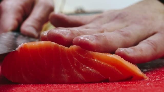 Cocinero-saca-los-huesos-del-filete-de-salmón-cortar-pescado-en-rodajas-para-cocinar-sushi-en-4-k-de-resolución-en-cámara-lenta