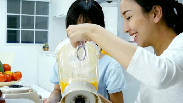 Madre-y-usando-poco-jugo-de-licuadora-en-la-cocina-Ellos-haciendo-jugo-de-naranja-para-beber-Personas-con-estilo-de-vida-y-el-concepto-saludable-