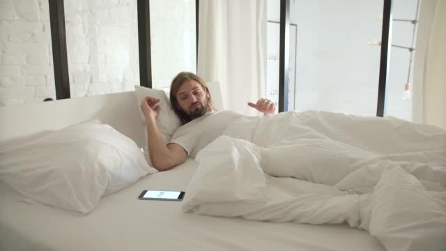Despierta-Hombre-durmiendo-en-la-cama-con-la-alarma-del-teléfono