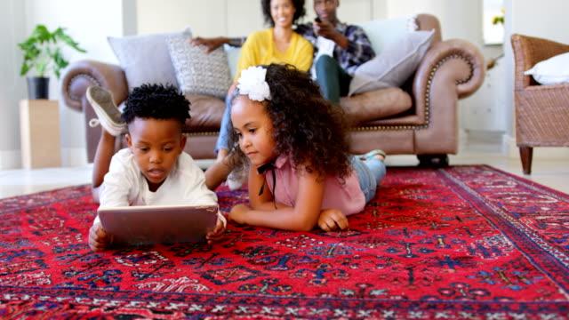 Vista-frontal-de-niños-negros-lindos-con-tableta-digital-en-sala-de-estar-en-casa-cómodo-4k