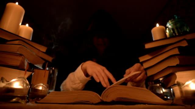 Una-niña-maga-de-primer-plano-mediana-en-una-capucha-en-una-habitación-oscura-a-la-luz-de-las-velas-y-en-busca-de-un-hechizo-que-da-vuelta-a-un-libro-Llave-baja-
